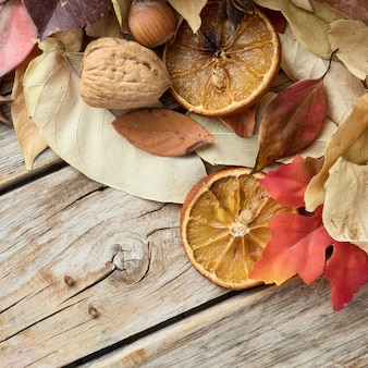 Top view of autumn leaves with walnut and dried citrus