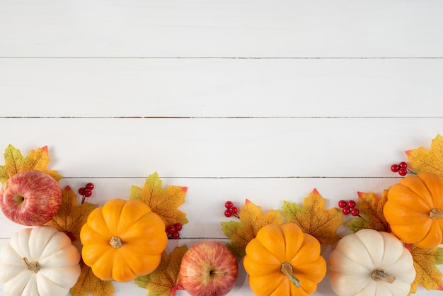 Top view of autumn maple leaves with pumpkins and red berries on white wood