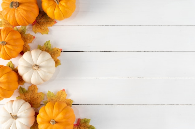 Top view of autumn maple leaves with pumpkins and red berries on white wooden background. thanksgiving day concept.