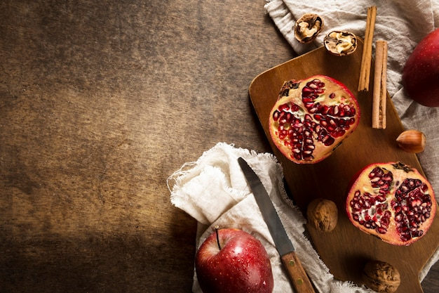 Top view of autumn pomegranates with copy space and cinnamon sticks