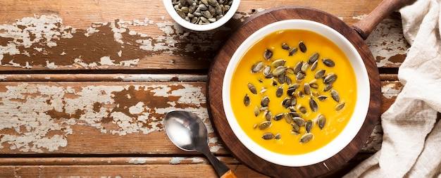Top view of autumn squash soup with seeds and copy space