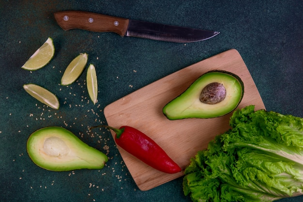 Top view avocado halves on a blackboard with lemon red pepper lettuce and knife on a dark green background