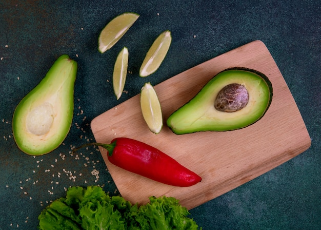 Вид сверху половинки авокадо на доске с красным перцем лимоном и листьями салата на темно-зеленом фоне