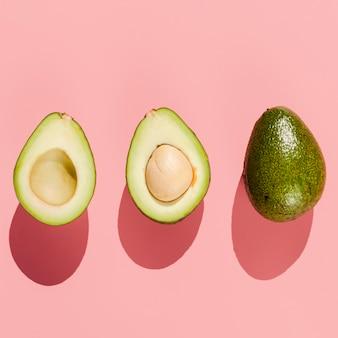 Вид сверху авокадо на розовом фоне