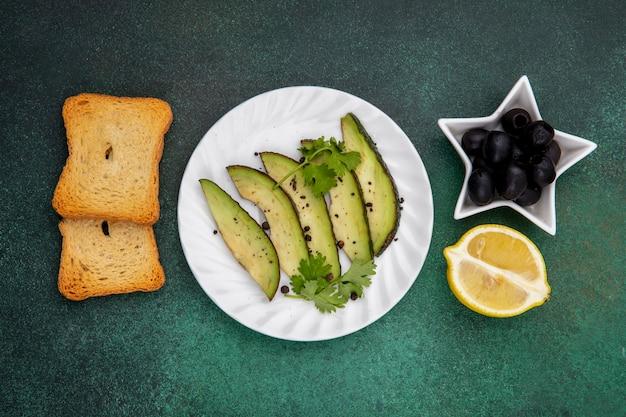 Vista dall'alto di fette di avocado sulla piastra bianca con olive nere fette di pane tostato e limone su gre