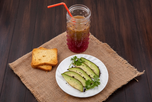 Top view of avocado slices on white plate with toasted bread slices and juice in a glass on sack cloth on wood