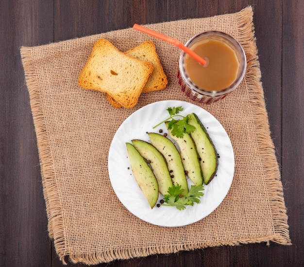Top view of avocado slices on white plate with toasted slice of bread with juice in a glass on sack cloth on wood