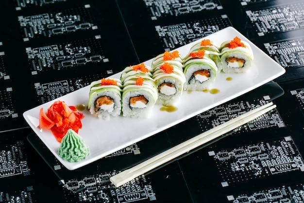Vista dall'alto di involtini di sushi di avocado con salmone condita con tobiko rosso
