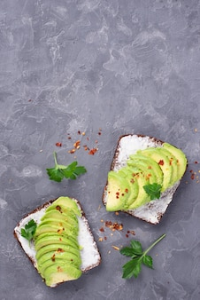 Top view of avocado toast with herbs and copy space