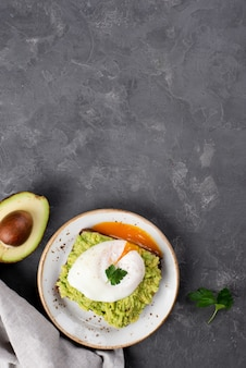 Top view of avocado toast with poached egg and copy space