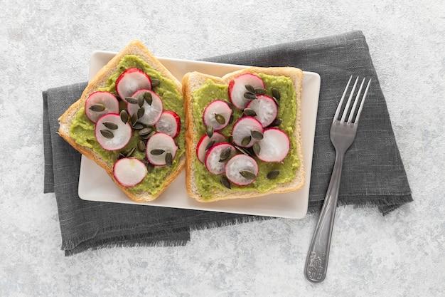Toast di avocado vista dall'alto con ravanello e semi sul piatto con forchetta