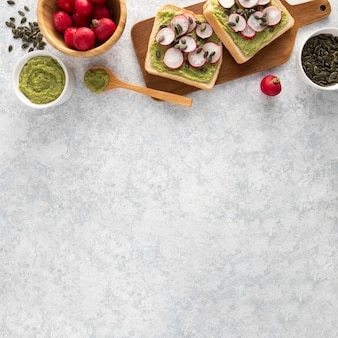 Top view avocado toast with radish and seeds with copy-space