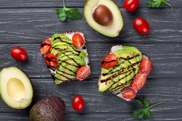 Top view of avocado toast with tomatoes and sauce