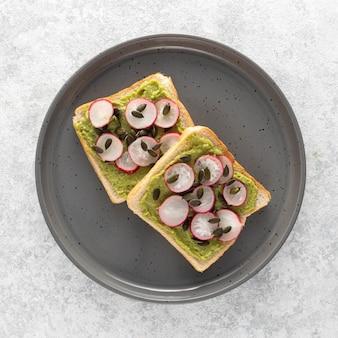 Toast di avocado con vista dall'alto con ravanello e semi