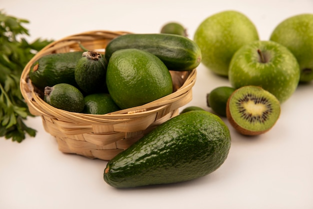 Vista dall'alto di avocado con cetriolo su un secchio con mele verdi e kiwi isolato su una superficie bianca