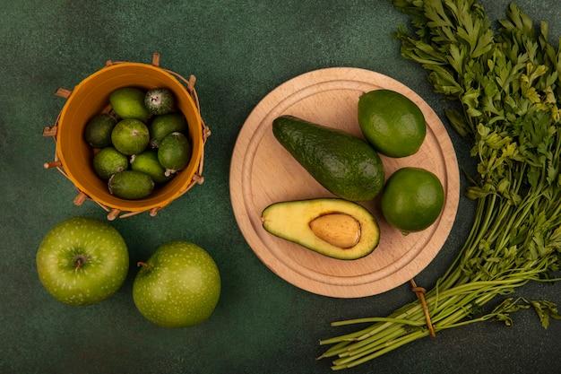 Vista dall'alto di avocado su una tavola da cucina in legno con lime con feijoas su un secchio con mele verdi e prezzemolo isolato su una parete verde
