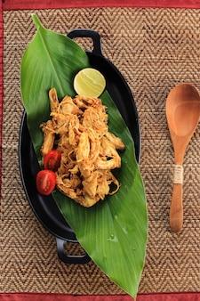 Top view ayam suwir bumbu kuning(ayam sisit with yellow spice)은 닭고기 덩어리로 만든 발리 또는 인도네시아 요리입니다. 검은 타원형 접시에 제공, 텍스트 또는 레시피 복사 공간