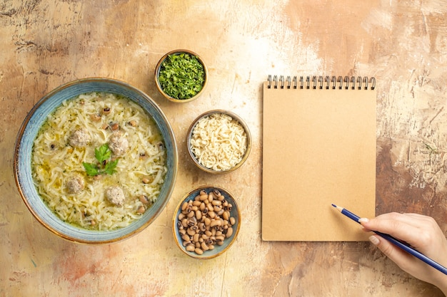 Top view azerbaijani erishte in bowl different stuffs in bowls blue pen in woman hand on notebook on beige background