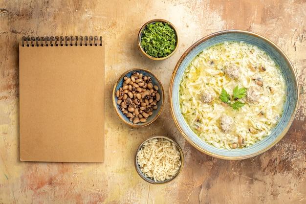 Vista dall'alto azero erishte in una ciotola diversi animali in ciotole un quaderno su sfondo beige