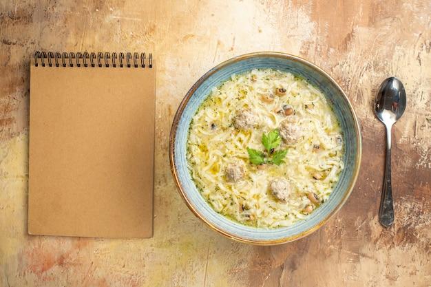 Vista dall'alto azero erishte in una ciotola un cucchiaio un quaderno su sfondo beige