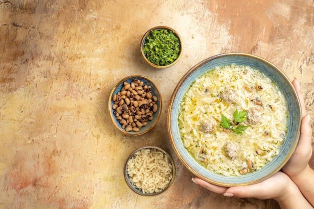 여자의 그릇에 있는 상위 뷰 아제르바이잔 에리슈테는 베이지색 배경의 그릇에 다른 물건을 손에 넣습니다.