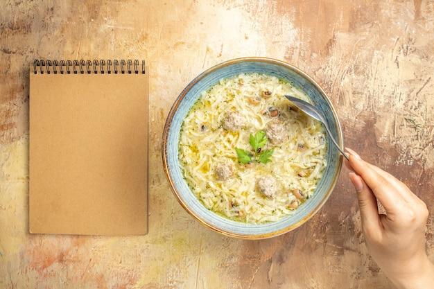 Vista dall'alto cucchiaio erishte azero in mano di donna in una ciotola un quaderno su sfondo beige