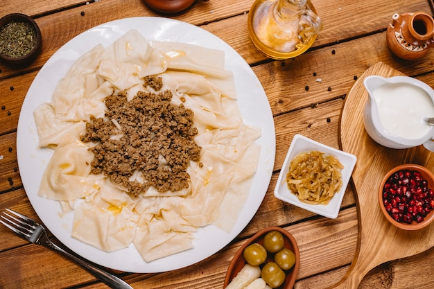 Top view of azerbaijani leaves khangal served with minced lamb meat and yogurt