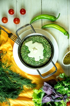 Top view of azerbaijani traditional kuku fried eggs with herbs served with sour yogurt in a pan