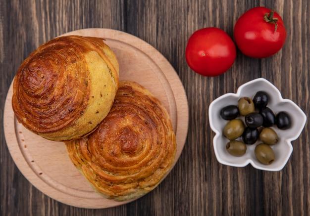 Vista dall'alto della pasticceria tradizionale azerbaigiana gogals su una tavola da cucina in legno con olive su una ciotola e pomodori freschi isolati su uno sfondo di legno