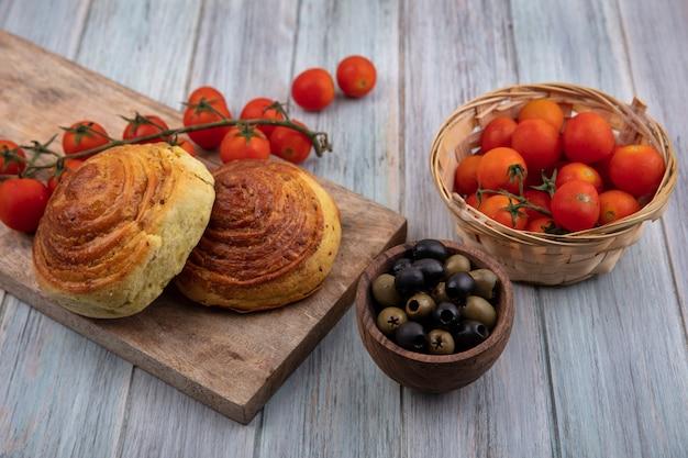 Vista dall'alto di gogals di pasticceria tradizionale azera su una tavola di cucina in legno con pomodori maturi con olive su una ciotola di legno su un fondo di legno grigio