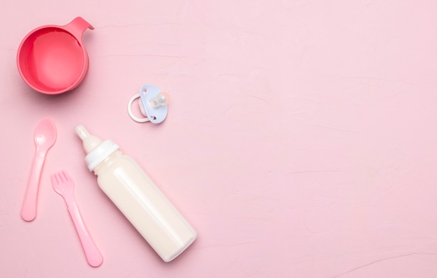 Top view of baby bottle with pacifier and copy space