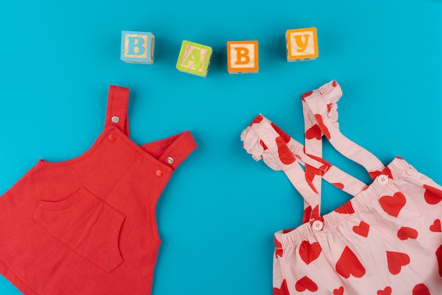 Top view of baby clothes on blue background