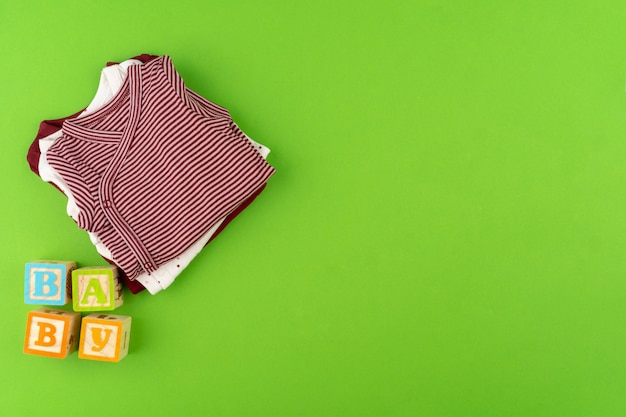Top view of baby clothes on green background