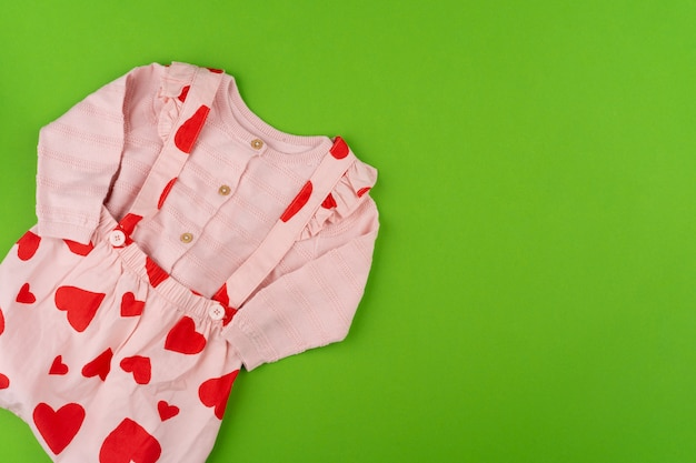 Top view of baby clothes on green surface