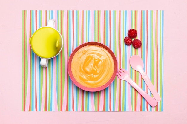 Top view of baby food in bowl with cutlery and fruit