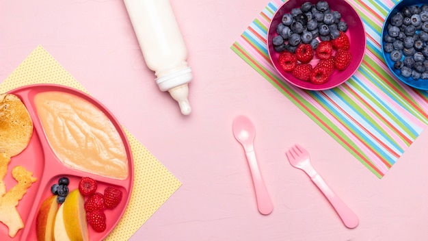 Top view of baby food with raspberries and baby bottle