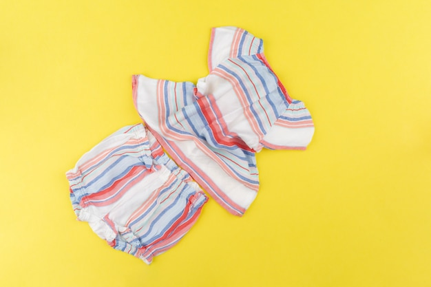 Top view of baby girl clothes on yellow background