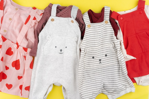 Top view of baby girl clothes on yellow