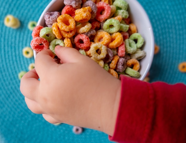 Top view of babys fingers touching cereals loops
