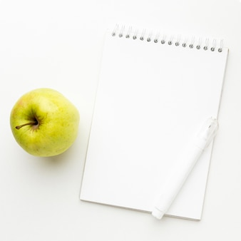 Top view of back to school essentials with apple and notebook