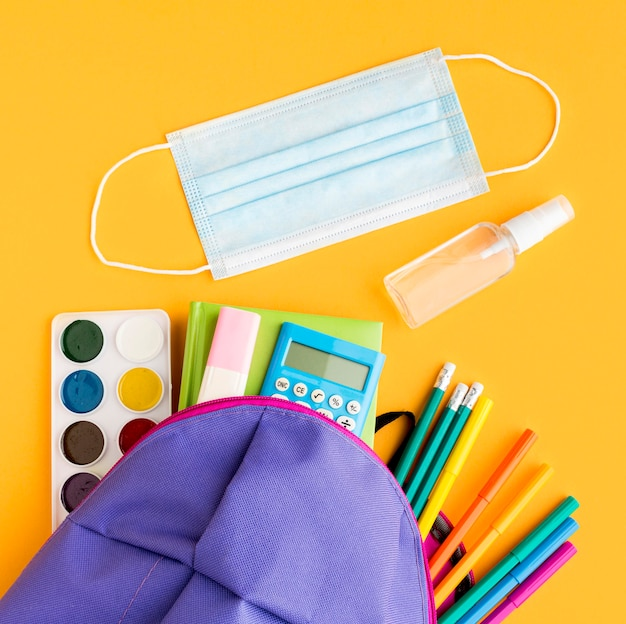 Top view of back to school essentials with backpack and medical mask