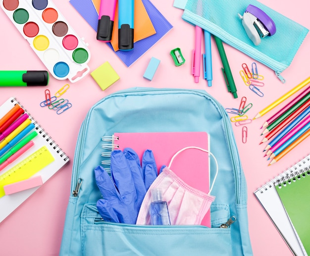 Top view of back to school essentials with backpack and watercolor