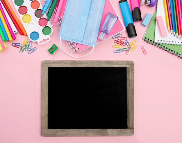 Top view of back to school essentials with blackboard and paper clips