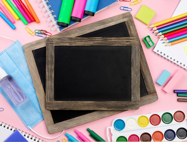 Top view of back to school essentials with blackboards and medical mask