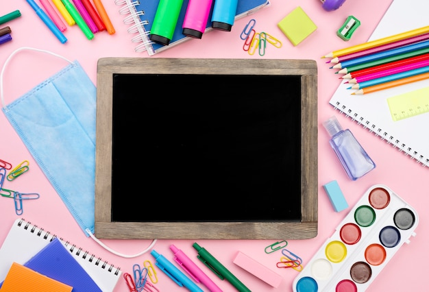 Top view of back to school essentials with medical mask and blackboard