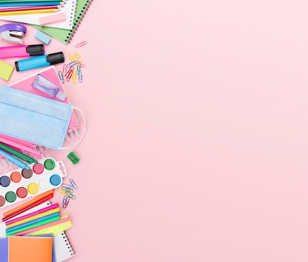 Top view of back to school essentials with medical mask and watercolor