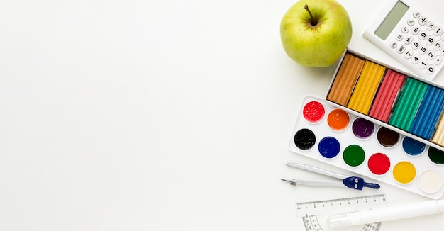 Top view of back to school essentials with watercolor and apple