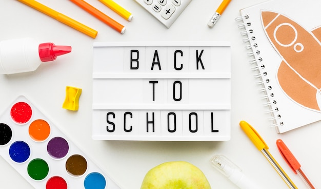 Top view of back to school essentials with watercolor and light box