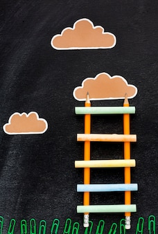 Top view of back to school ladder with pencils and clouds