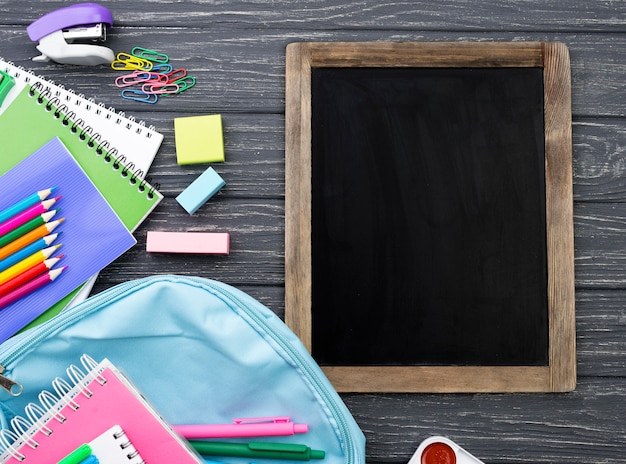 Top view of back to school stationery with backpack and blackboard